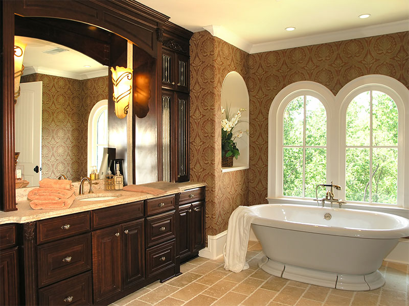 A custom bathroom design with a distinctive masculine feel, with dark cabinetry and free standing tub.