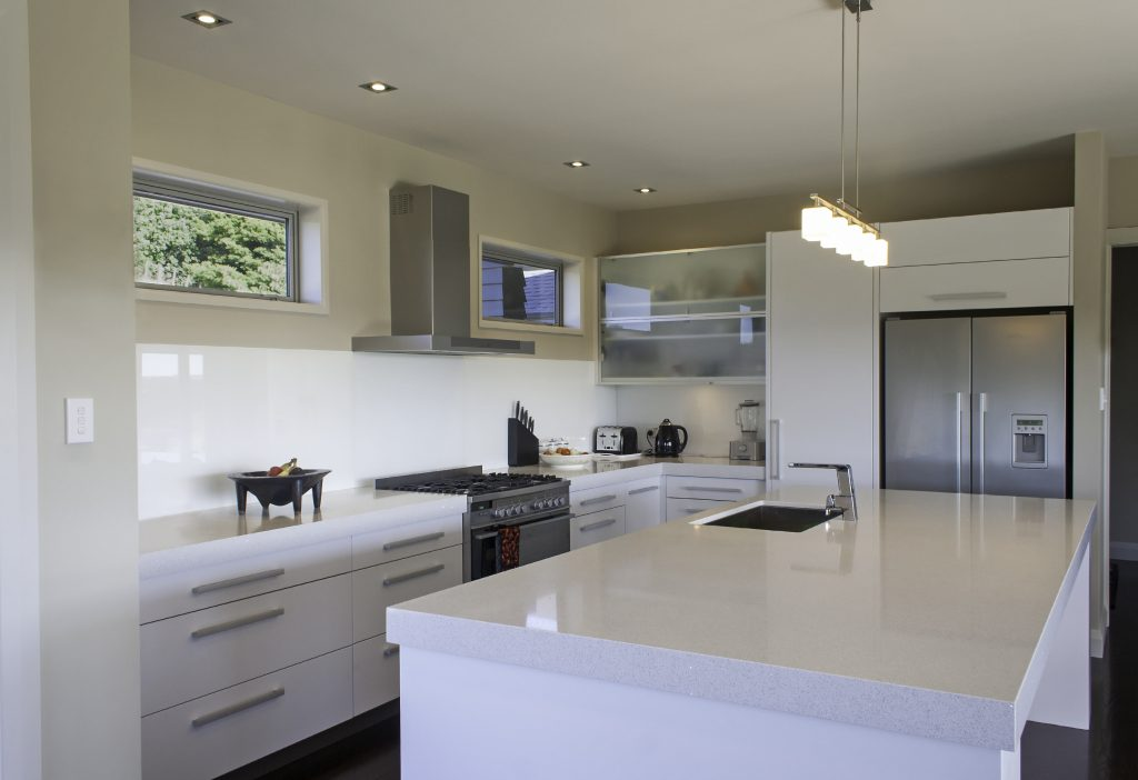 Custom kitchen remodeling in white with stainless accents.