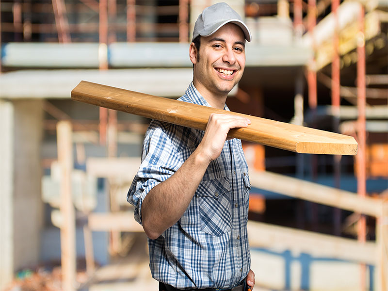 carpenter carrying lumber for custom home construction Jacksonville FL